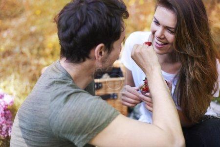 Photo pour Beau jeune couple heureux en amour manger sur rendez-vous romantique dans le parc - image libre de droit