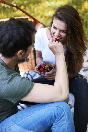 Photo for Beautiful young couple in love eating strawberry in park while date - Royalty Free Image