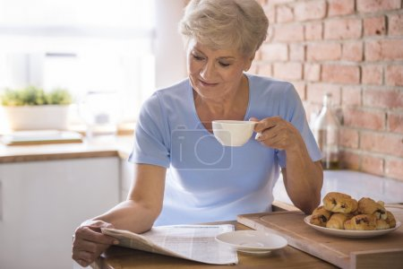 woman drinking tea and reading paper