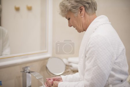 mature woman washing hands