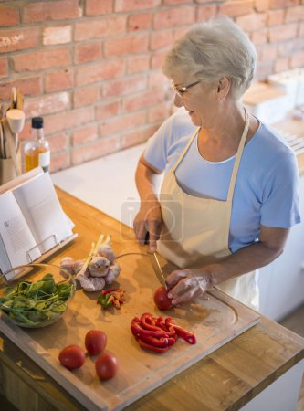 Photo for Beautiful mature woman preparing tasty food in kitchen - Royalty Free Image