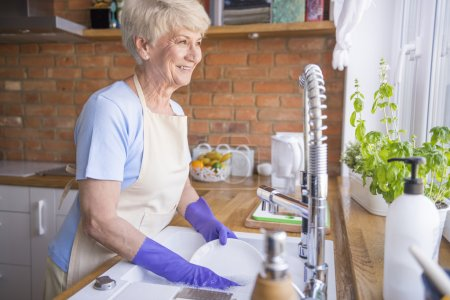 mature woman washing plates in kitchen