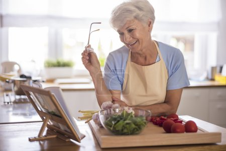 Photo for Beautiful mature woman looking to recipe book while preparing tasty food in kitchen - Royalty Free Image