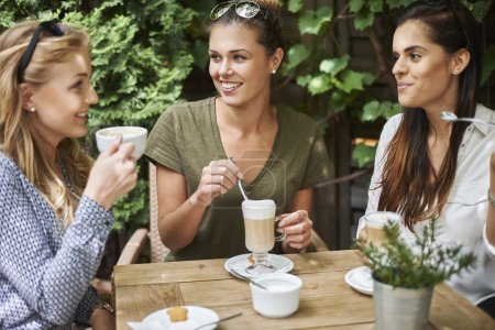Photo for Attractive women spending time together in cafe - Royalty Free Image