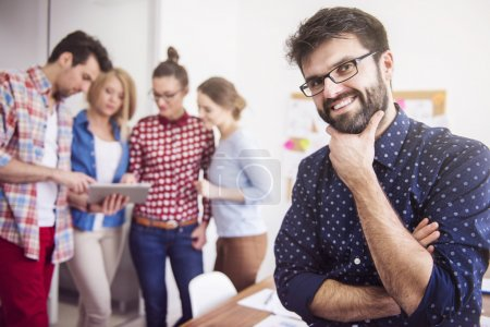 Photo for Businessman with hand on chin and funny colleagues in background working together in office - Royalty Free Image