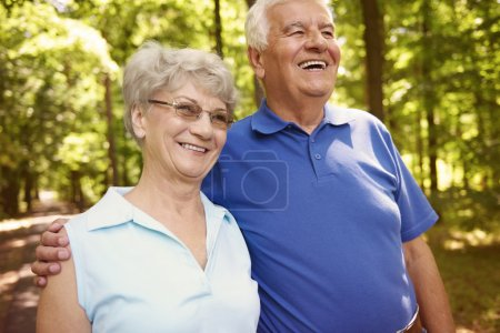 Photo for Happy senior couple walks in the park. Activity is very important at the elder age - Royalty Free Image