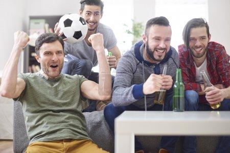Men watching a match on TV
