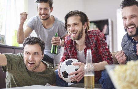 Friends watching soccer match.