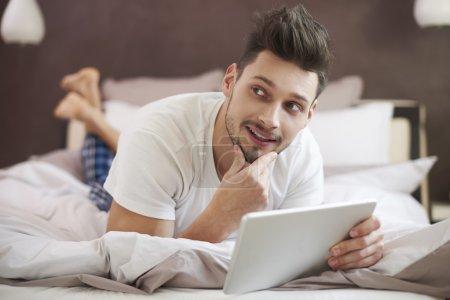 Photo pour Homme Détente dans le lit avec tablette numérique - image libre de droit