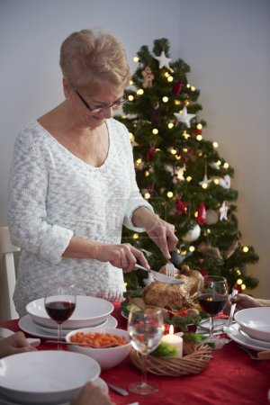Photo for Cheerful grandmother cutting turkey on christmas - Royalty Free Image