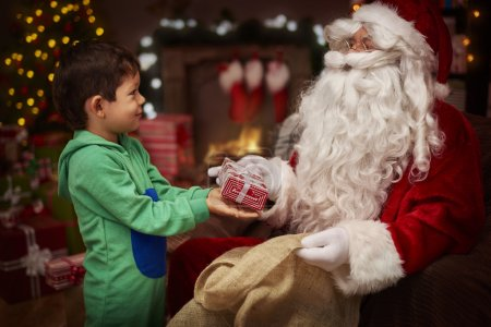 Photo for Happy boy takes christmas present from Santa - Royalty Free Image