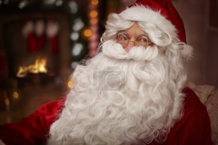 Photo for Santa Claus with white beard. Santa claus warming up next to the fireplace - Royalty Free Image