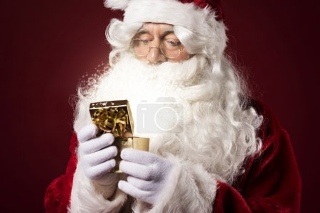 Photo for Santa Claus open gift box. Small present doesn't mean it's less important - Royalty Free Image