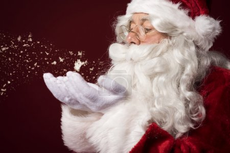Photo for Santa claus blowing some snowflakes - Royalty Free Image