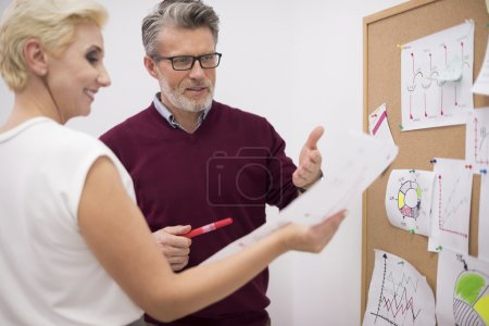 Photo pour Homme d'affaires et femme d'affaires travaillant dans le bureau près de la planche de liège - image libre de droit
