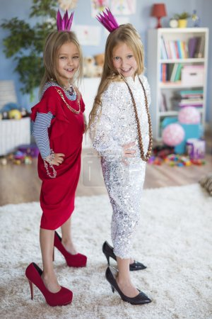 Photo for Little girls dreaming of becoming adults with clothes and cosmetics - Royalty Free Image