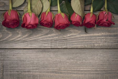 Photo for Valentine's decoration on the wooden planks, frame of beautiful red roses - Royalty Free Image