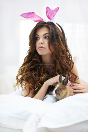 Little rabbit with sexy woman in the bed