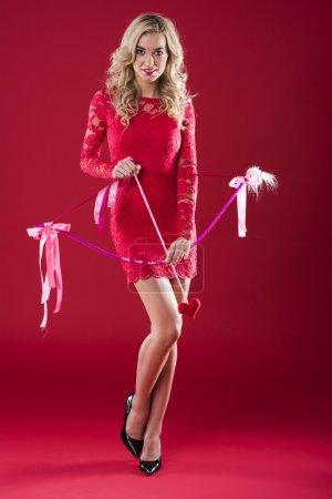 Photo pour Femme sur fond rouge avec une flèche de Cupidon - image libre de droit