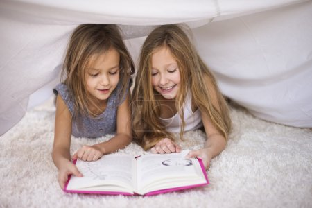 Sisters reading their favorite book
