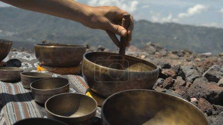 Photo pour Un jeune asiatique jouant Tibedt chantant des tasses de cuivre sur une montagne dans la nature - image libre de droit