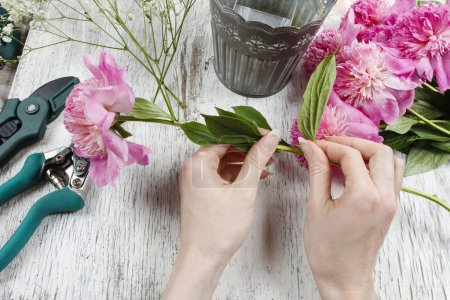 Florist at work. Woman making spring floral decorations of pink
