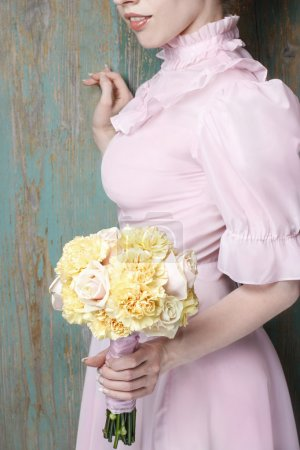 Photo pour Woman holding bouquet of yellow carnation and pink pastel roses. Party decoration - image libre de droit