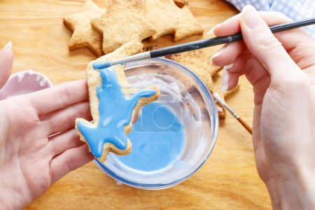 Decorating gingerbread cookies with blue and white icing.
