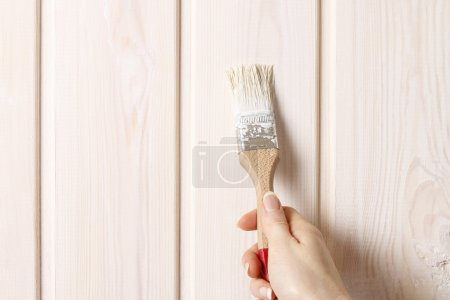 Woman painting wood
