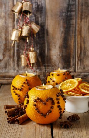 Photo for Orange pomander ball with candle decorated with cloves in heart shape. Party decoration - Royalty Free Image
