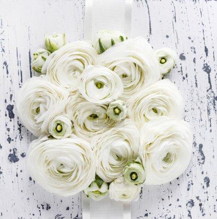 White ranunculus flowers on white wooden background. Wedding pos