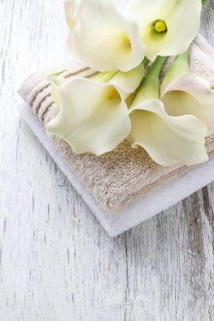 Photo pour Serviettes et bouquet de fleurs calla blanc sur une table en bois rustique - image libre de droit