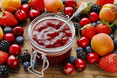 Jar of strawberry jams among summer and autumn fruits