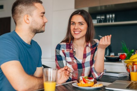 junges Paar sitzt in der Küche und probiert Capcakes mit