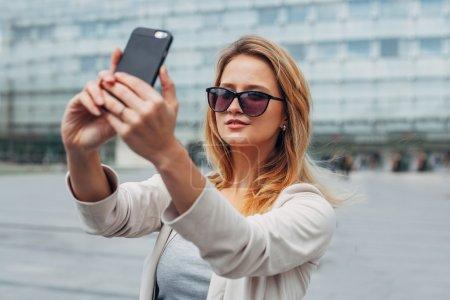 Girl taking selfie. Urban background.
