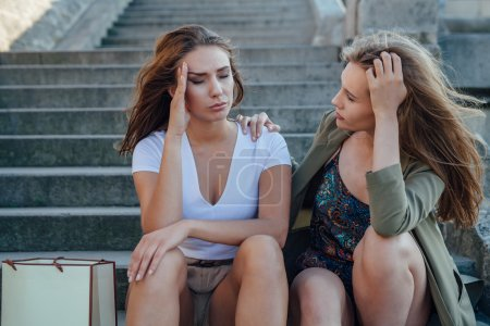 Photo pour Deux jeunes filles assises dans les escaliers. L'une encourage son amie - image libre de droit