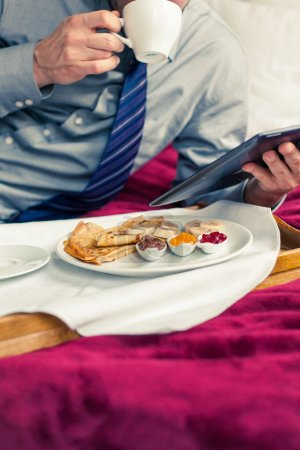 Businessman working on tablet during breakfast