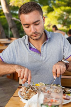 Photo for Young man sitting behind the table and eating seafod - Royalty Free Image