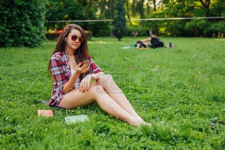 Photo pour Belle femme écouter de la musique aujourd'hui dans le parc - image libre de droit