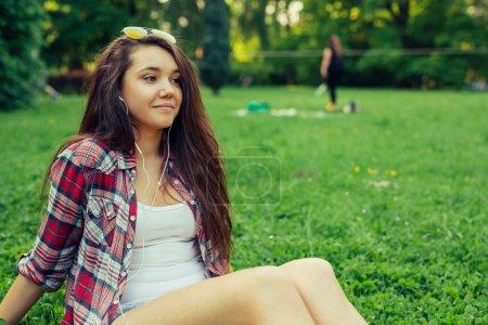 Photo pour Brune fille de cheveux assis sur l'herbe dans le parc et posant à l'image - image libre de droit