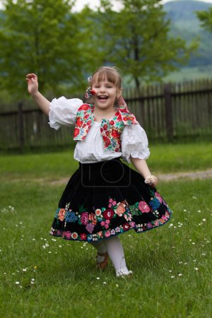 Photo for Little girl in costume running around the meadow with flowers - Royalty Free Image