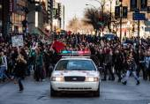 Policejní auto před demonstranty, řízení provozu