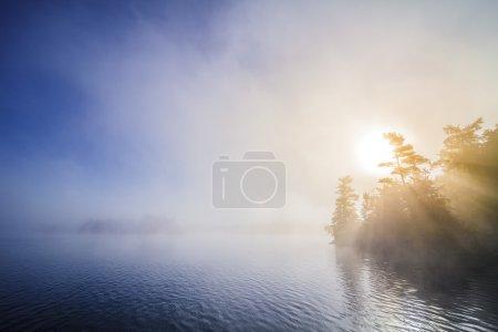 Photo pour Calme lac brumeux le matin avec beaux rayons de soleil - image libre de droit