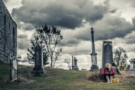 Photo for Lonely Sad Young Woman with Sunflowers in front of a Gravestone in a Cemetery - Royalty Free Image