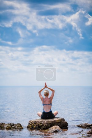 Photo for Young Woman doing Lotus Yoga Position in Front of the Ocean - Royalty Free Image