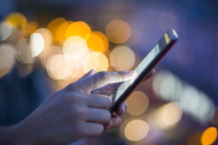 Photo pour Femme tenant téléphone portable dans les mains sur fond de puits de lumière nocturne de la ville - image libre de droit