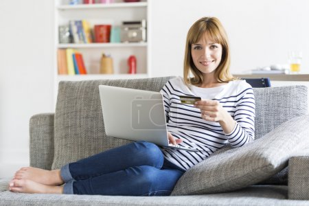 Photo for Mid adult woman shopping using laptop and credit card in modern apartment. Ecommerce - Royalty Free Image