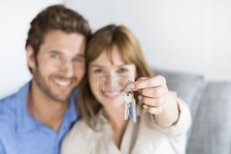 Cheerful thirty year old  couple showing a keys of their new apa
