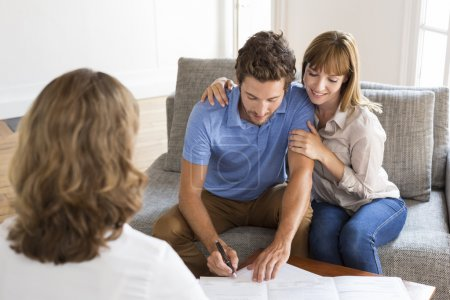 Young couple owners signing a contract with real estate agent for house purchase