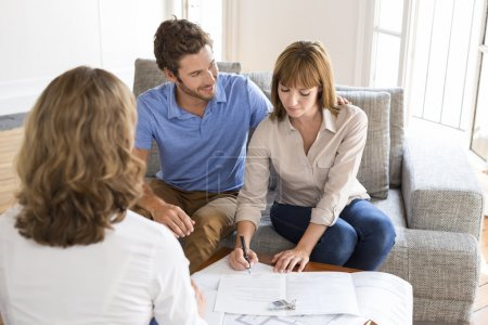 Owners couple signing a contract with real estate agent for house investmen